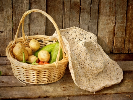 Vintage textured image of a basket of fresh picked organic vegetables and a straw hat on a grunge wood background