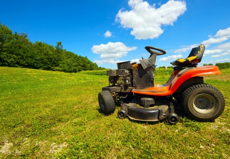 corn island: Wide angle image of an old mower at rest on a farm against a beautiful blue and cloudy sky on a farm on Manitoulin Island, Canada in the summer time   Stock Photo