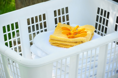 Close up image of a basket with freshly dried and folded towels and washcloths just of the clothesline in the early morning