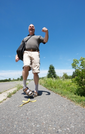 sandal tree: Humorous wide angle image of a middle aged nerd happily strolling down the street and is about to slip on a banana peel on a sunny summer afternoon with copy space.