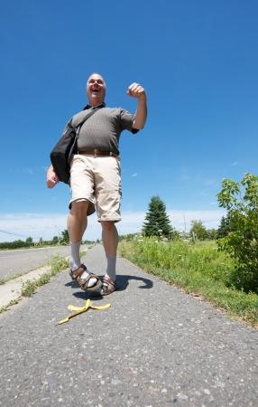 sandal tree: Imagen chistosa de un gran angular de mediana edad empoll�n feliz paseando por la calle y est� a punto de resbalar en una c�scara de pl�tano en una soleada tarde de verano con copia espacio. Foto de archivo