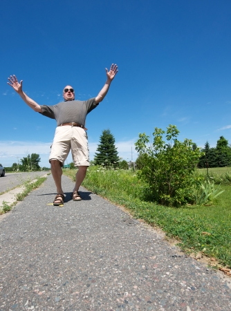 Humorous wide angle image of a cool, arrogant looking middle aged man walking down the street slipping on a banana peel on a sunny summer afternoon with copy space.