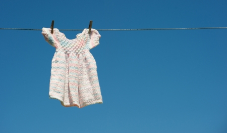 A grandmothers hand knitted baby dress hangs drying on a clothesline against a brilliant blue sky with copy space.  Stock Photo