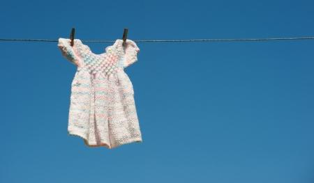 Une main-m�res b�b� robe tricot�e pend s�cher sur une corde � linge contre un ciel bleu brillant avec copie espace.