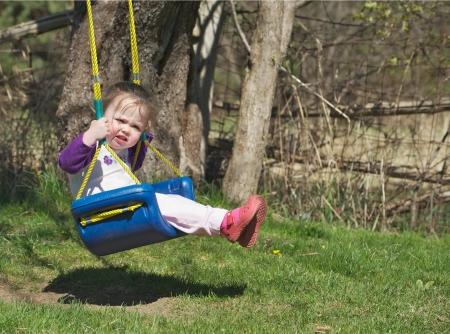 Un bambin doux petit jeu � l'ext�rieur sur son swing au soleil au printemps