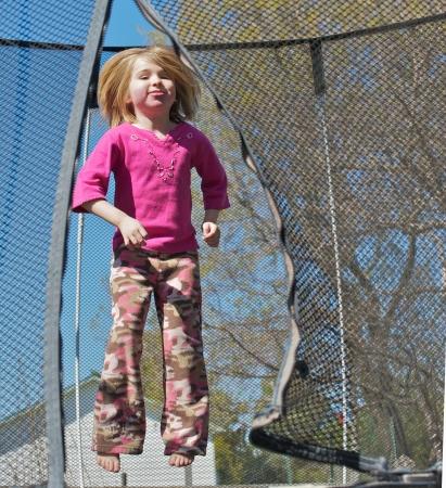 A cute little girl having fun jumping in her trampoline