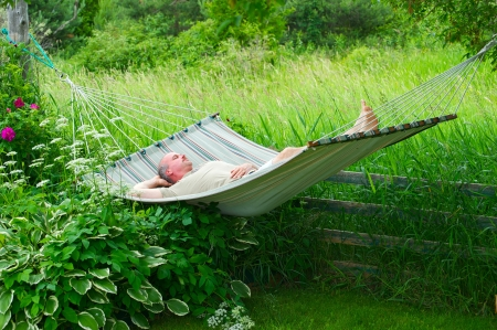 Nice image of a middle aged man relaxing in a hammock in the shade on a hot summer day