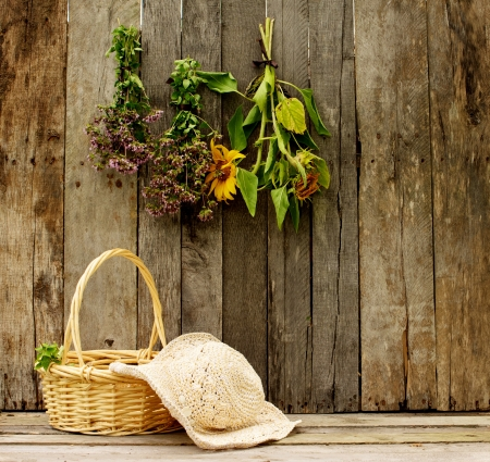high contrast: Richly toned image of a gardener s straw hat and basket of freshly cut oregano and a aged barn board background