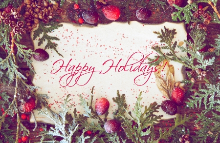 richly: Richly toned Christmas card with with cedar sprigs, berries and other natural decorations framing an old paper center with text  Happy Holidays