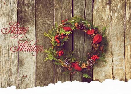 가정을 특징으로 크리스마스 카드의 디자인은 자연 장식 텍스트 해피 홀리데이 소박한 나무 벽에 매달려 크리스마스 화 환을 만든