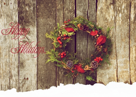 Christmas card design featuring a home made christmas wreath with natural decorations hanging on a rustic wooden wall with text  Happy Holidays