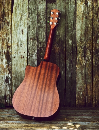 Vintage style image of a classical guitar on a grunge wood backdrop with copy space, back view