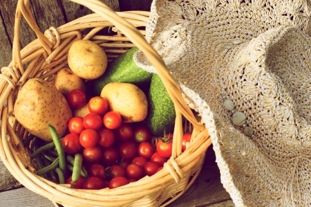 harvest basket: Abstract closeup vintage style image of a basket of fresh picked organic vegetables and a straw hat on a grunge wood background   Stock Photo