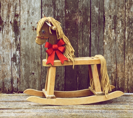 Richly toned vintage style image of an antique rocking horse with a sparkling red Christmas bow around his neck on a rustic wooden backdrop   Stock Photo