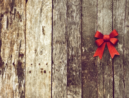 Richly toned, high contrast Christmas background with a sparkling red Christmas bow on a grunge wooden backdrop with copy space