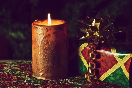 richly: Richly toned, close up image of a burning Christmas candle and gift with copy space.  Stock Photo