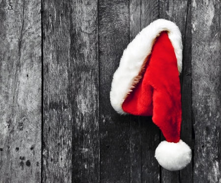 Santa s hat hanging on a desaturated grunge wood background