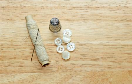 kit de costura: Costura. Hilo, una aguja, un dedal, y algunos botones en un fondo de madera.