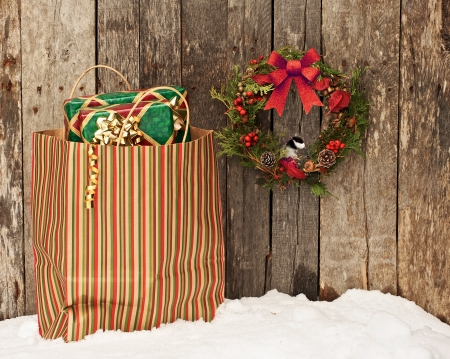Christmas wreath with a little chickadee peeking out hanging on a rustic wooden wall beside a colorful bag filled with Christmas gifts