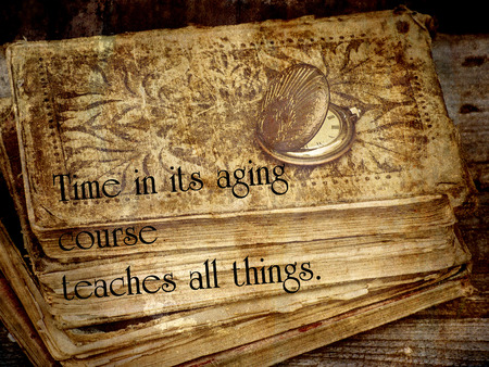 Inspirational quote on time on textured backgound with an old pocket watch, and a stack of antique books.
