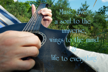 philosophy of music: Inspirational quote on music, with a man composing music, laying in his hammock. Stock Photo
