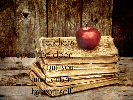 Inspirational quote regarding education on a grunge textured background with a stack of antique books, and an apple.
