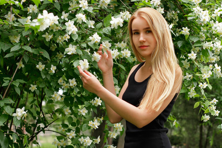 Young girl near blossoming white flowers Stock Photo