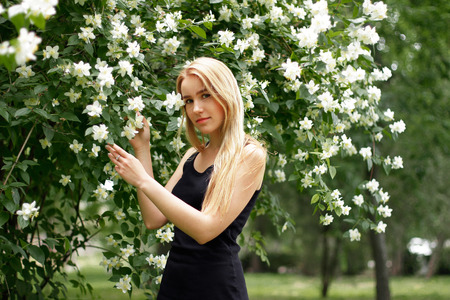 Beautiful young girl with long white hair near blooming flowers