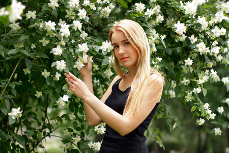fair skin: Beautiful young blond girl near blooming white flowers