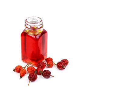 Bottle of rose hip oil and dry rose hips Standard-Bild