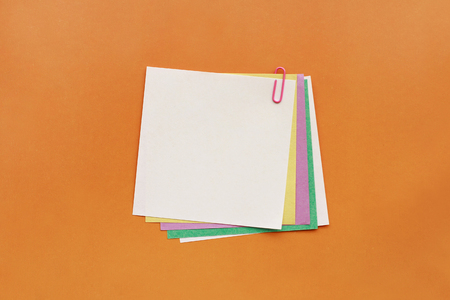 A lot of colored paper fastened pink paperclip on orange background 写真素材