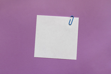 White note paper label with clip on purple background Stock fotó
