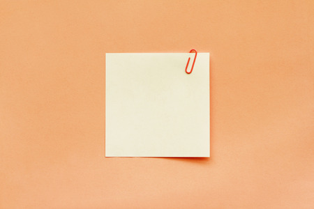 White note paper label with clip on orange background