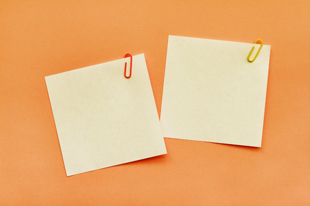 Two white adhesive note papers with clips on orange background Zdjęcie Seryjne