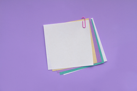 Blank note papers with clip on purple background Standard-Bild