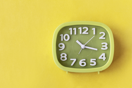 Green clock with white numbers and arrows on yellow background 写真素材