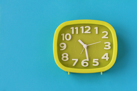 Green clock with white numbers and arrows on blue background