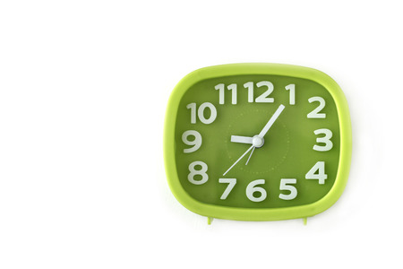 Green clock with white numbers and arrows on white background 写真素材