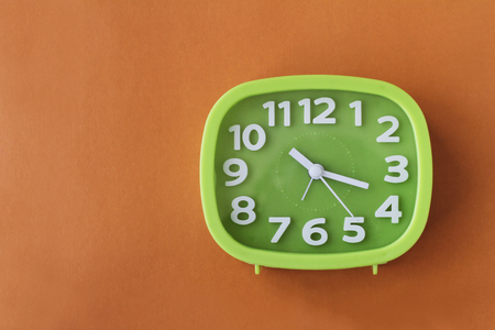 Green clock with white numbers and arrows on orange background