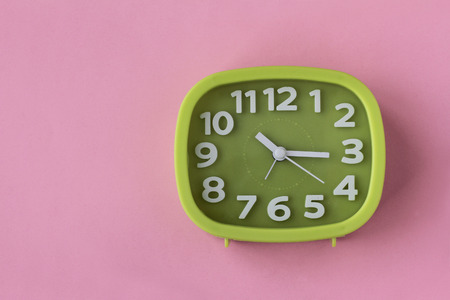 Green clock with white numbers and arrows on pink background 写真素材 - 100660319
