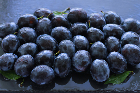 Ripe juicy plums sprayed with water on slate board
