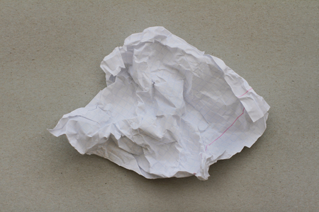 Crumpled sheet of white paper on cardboard