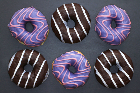 Donuts of violet and chocolate colored with striped pattern on dark background