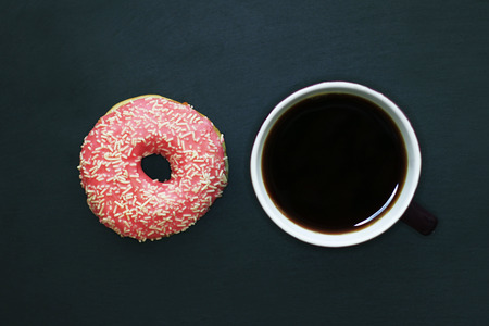 Donut in pink glaze and cup of coffee on dark background, view from above