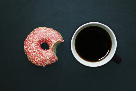 Bitten donut in pink glaze and cup of coffee on dark background, view from above
