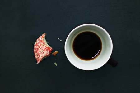 Donut uneaten and half-full coffee cup on dark background, view from above