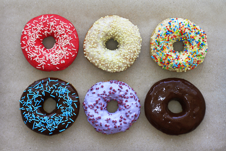 Donuts of different colors on cardboard, view from above