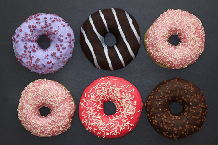 Donuts of different colors on a dark background, view from above 写真素材