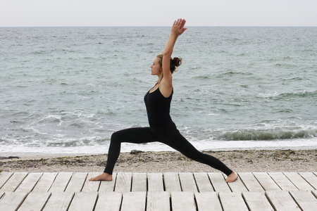 Young woman doing yoga at the seaside in the morning on summer day 写真素材