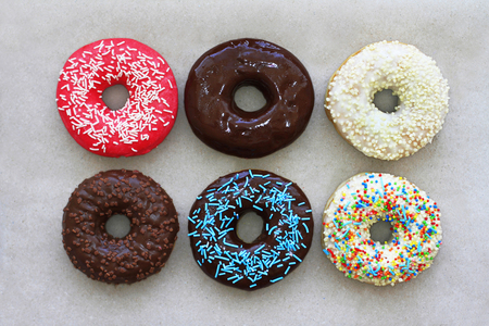 Donuts of different colors on cardboard, top view Stock Photo